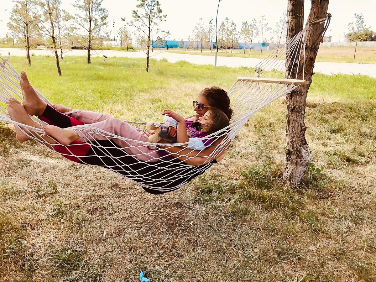 Snuggling in a hammock in a green area on campus, Anna and her daughter take a break to chat while their son snaps a photo of the pair.