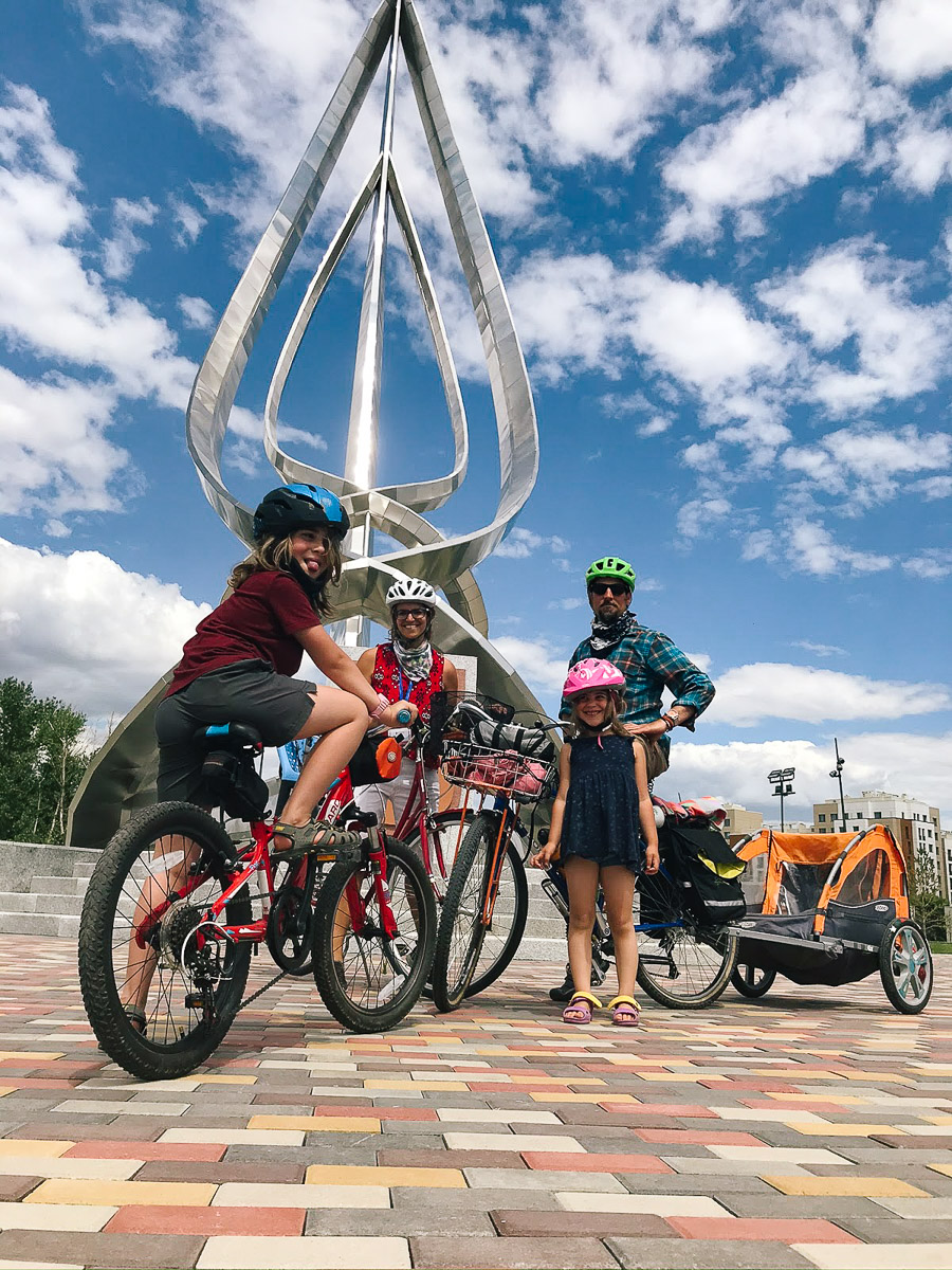 The family poses for a bike-y picture on campus against the expansion blue skies of Kazakhstan. Three bikes can be seen including the red step-thru with blue bike seat and an orange trailer. In the background is a large metal sculpture on campus in an area where a previous graduation celebration took place.