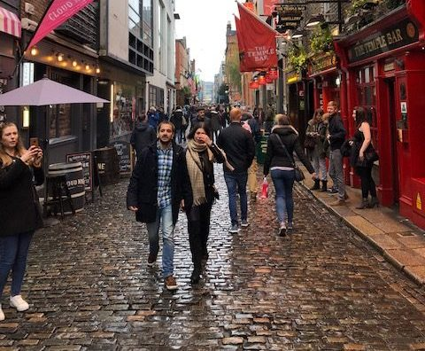 A couple walks through a crowded Dublin city street