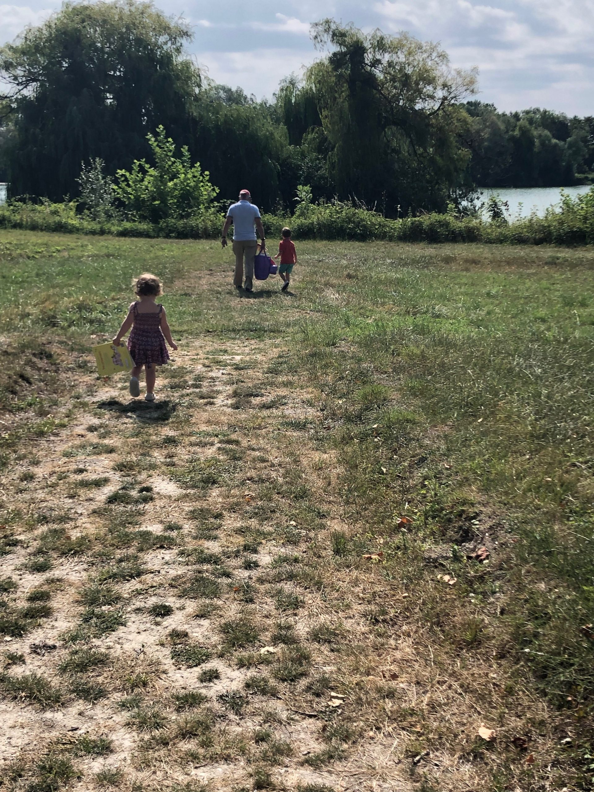 family walk to lake to swim at the chateau de juvigny Burgundy