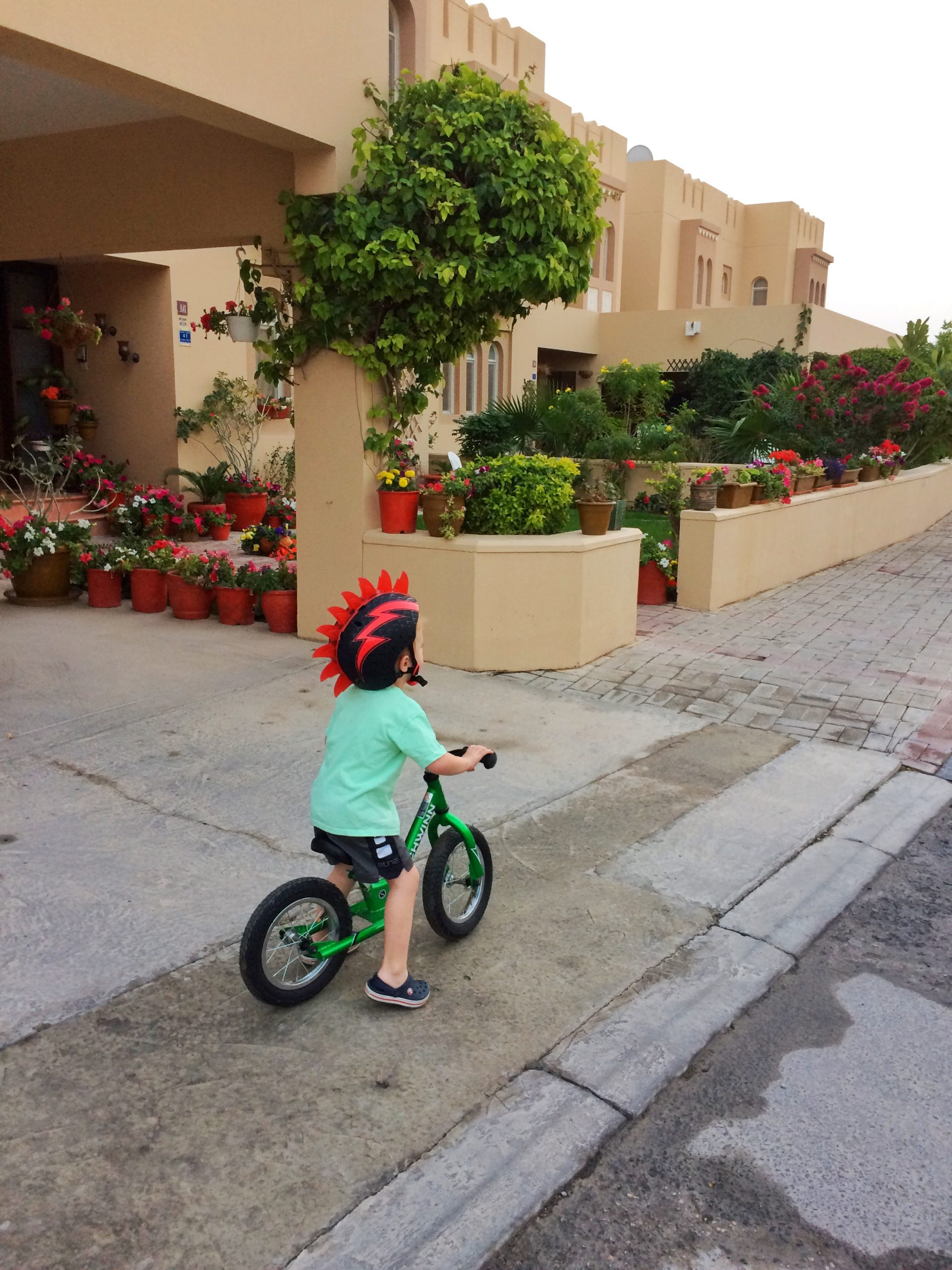 Toddler riding his bike on a compound in the Middle East