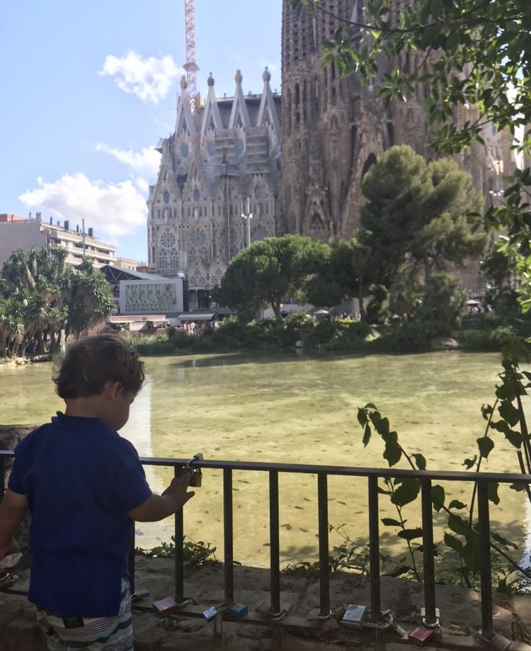 Toddler boy looking at the water near Sagrada Familia in Barcelona, Spain