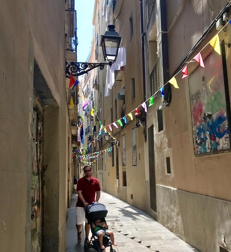 Father walking toddler son in a stroller through El Born area of Barcelona, Spain