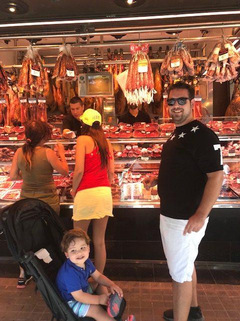 Father and son at a meat stand at Mercado de La Boqueria in Barcelona, Spain