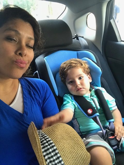 Mother posing with child in car seat