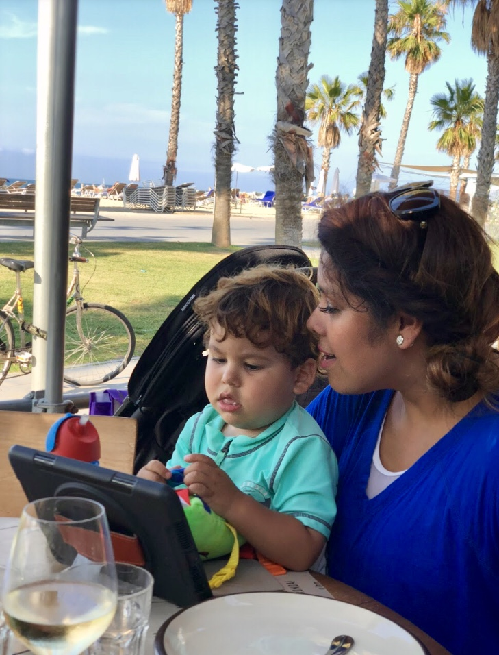 Mother and son looking at a menu sitting at the beach in Barcelona, Spain
