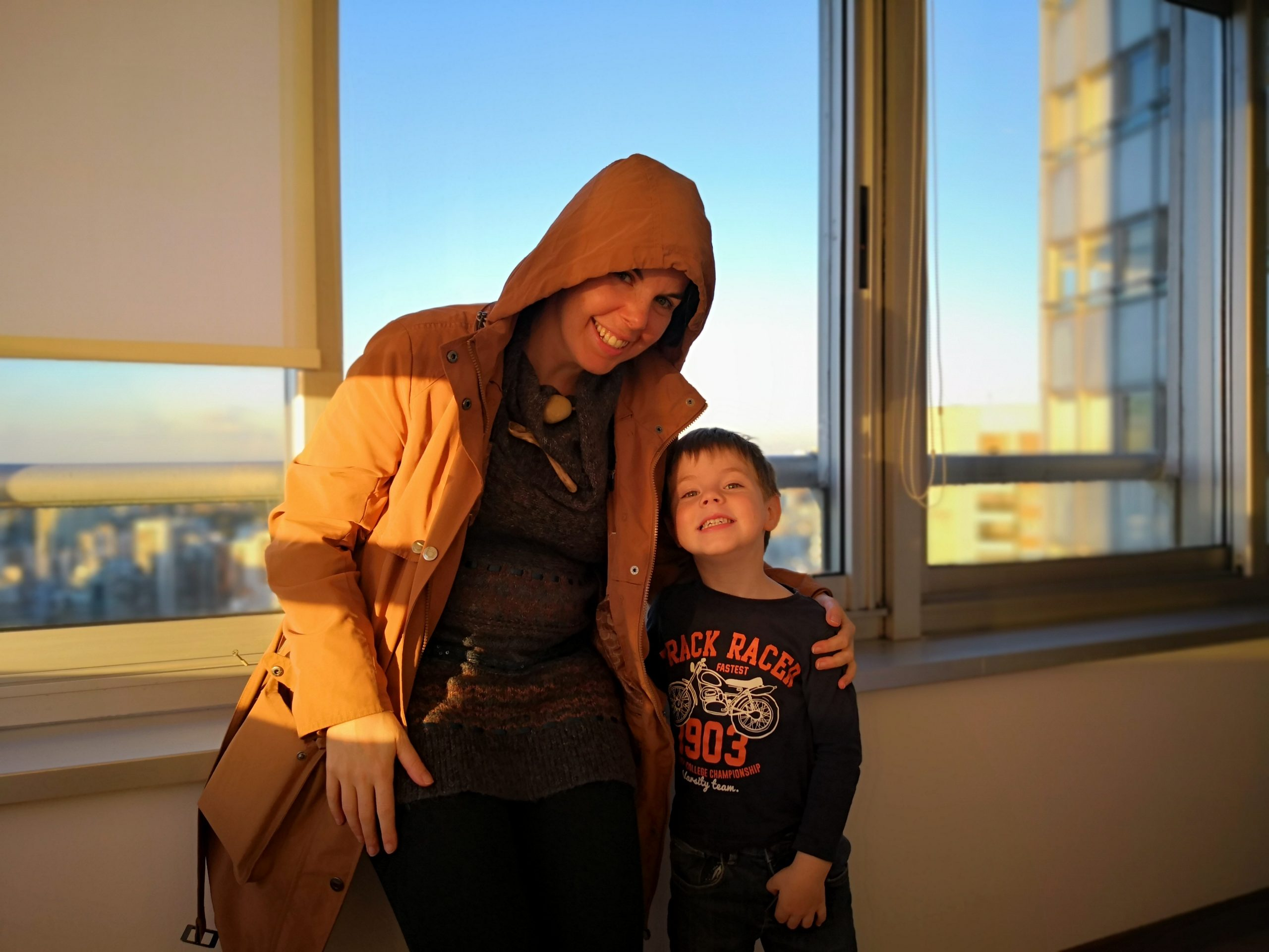Marianne wearing the Rhonda Travel Trench Coat with her son beside her