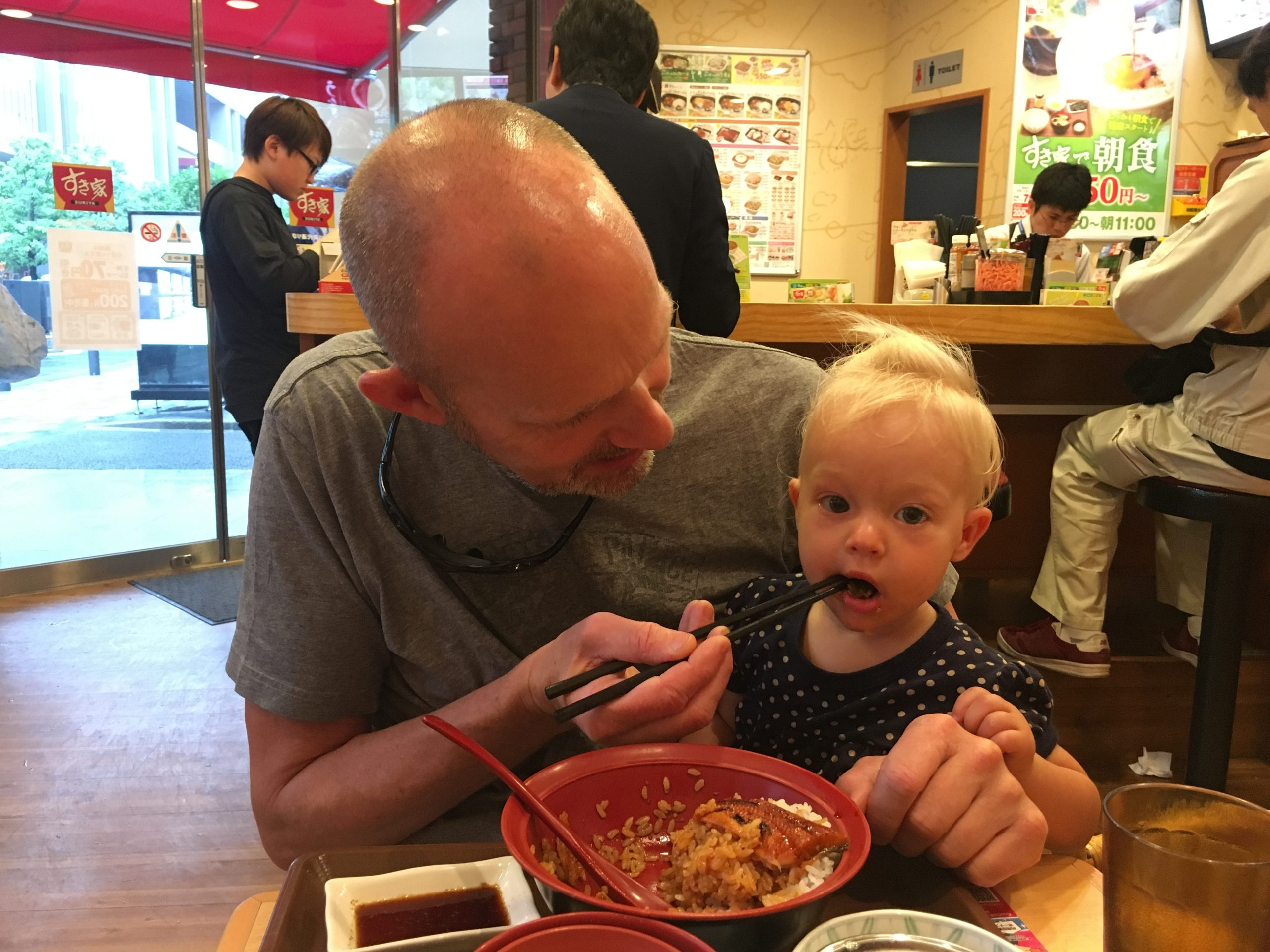 Toddler girl eating a rice bowl with father in Japan using chopsticks
