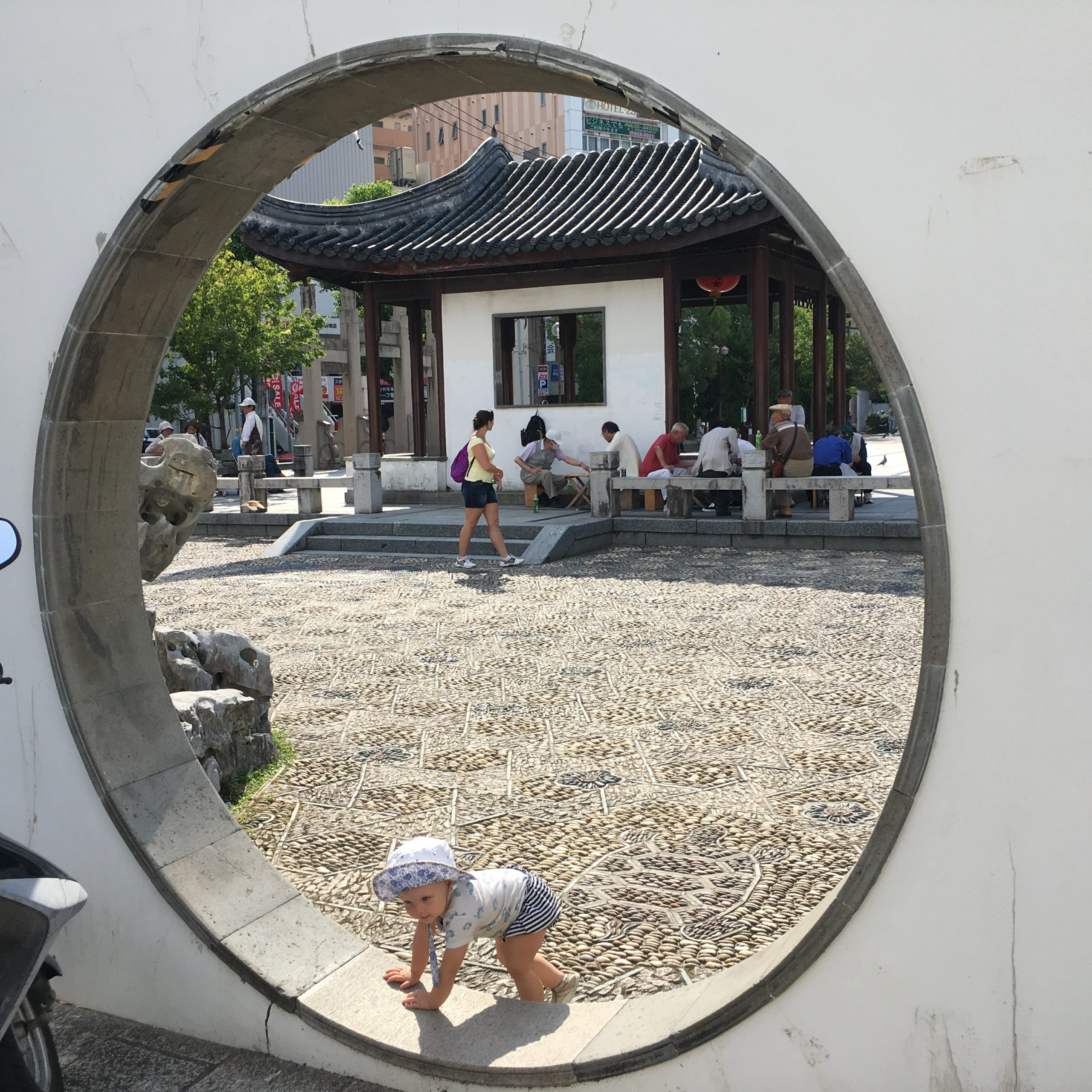 Toddler girl climbing on a circular wall in Japan