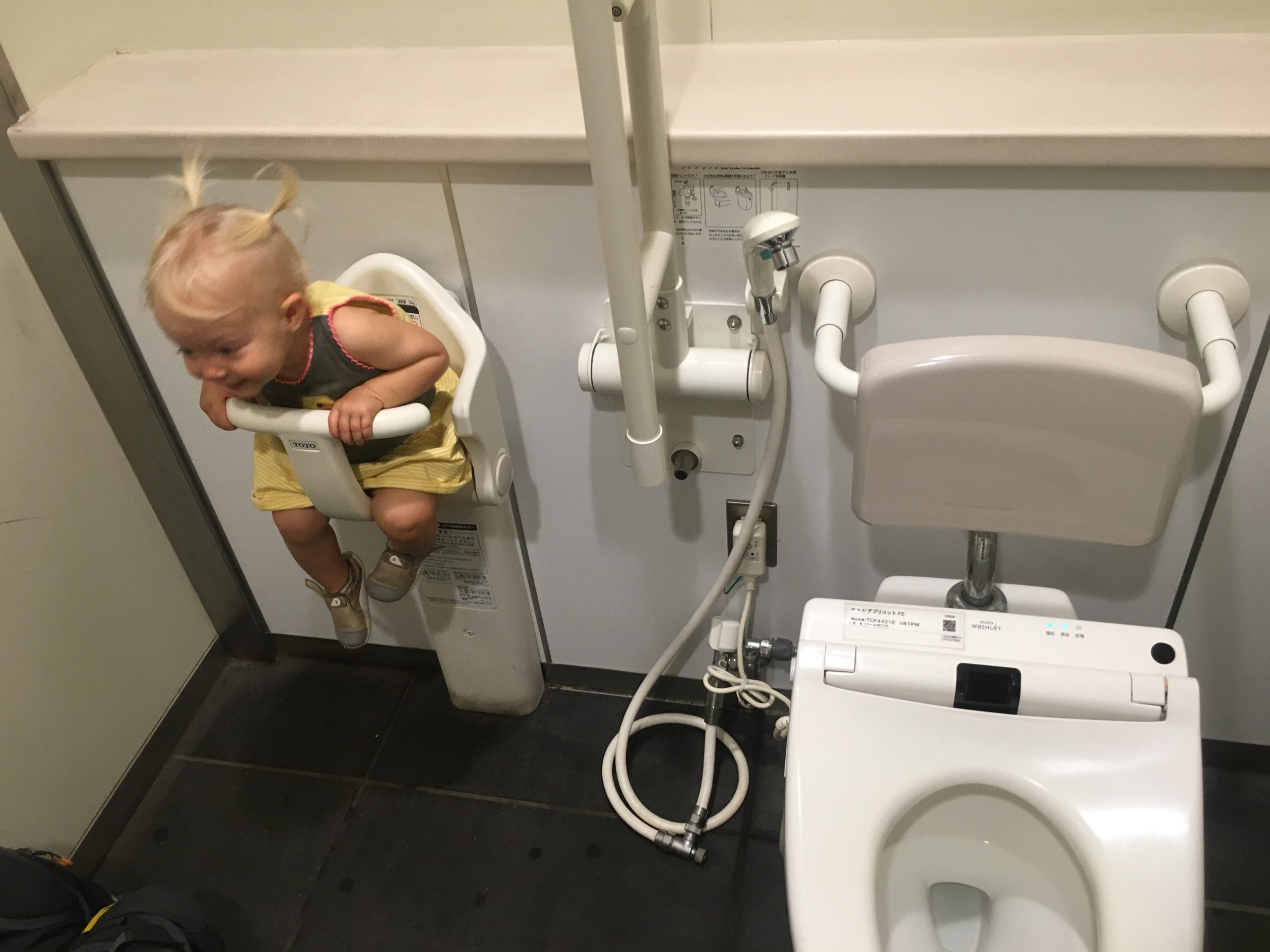 Toddler girl sitting in a child seat in a public bathroom in Japan