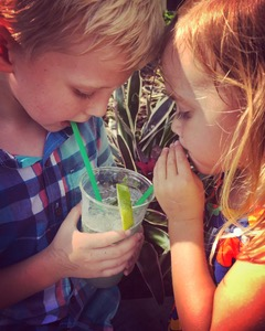 Two kids sharing a cold drink