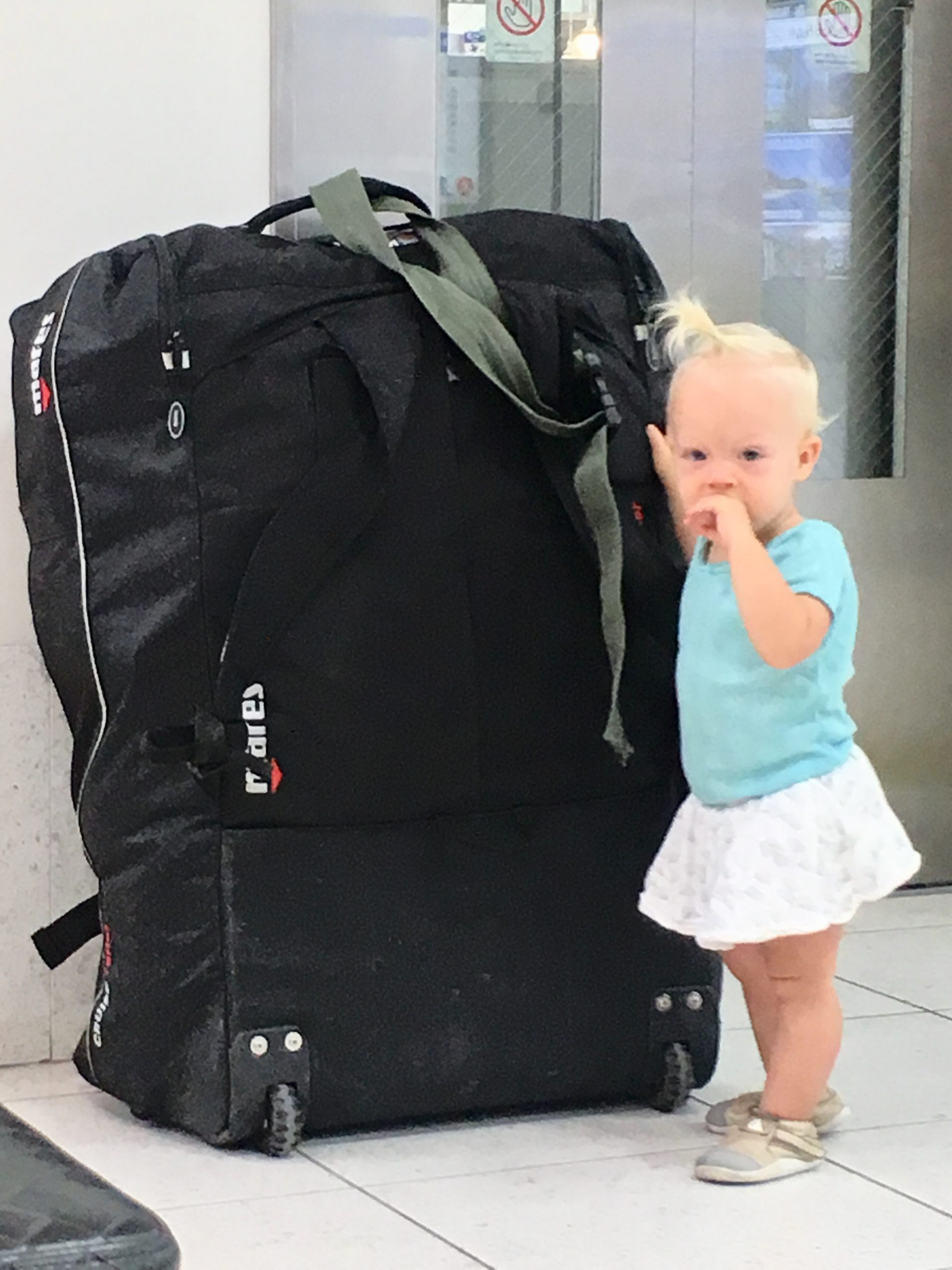 Toddler girl standing with a large suitcase