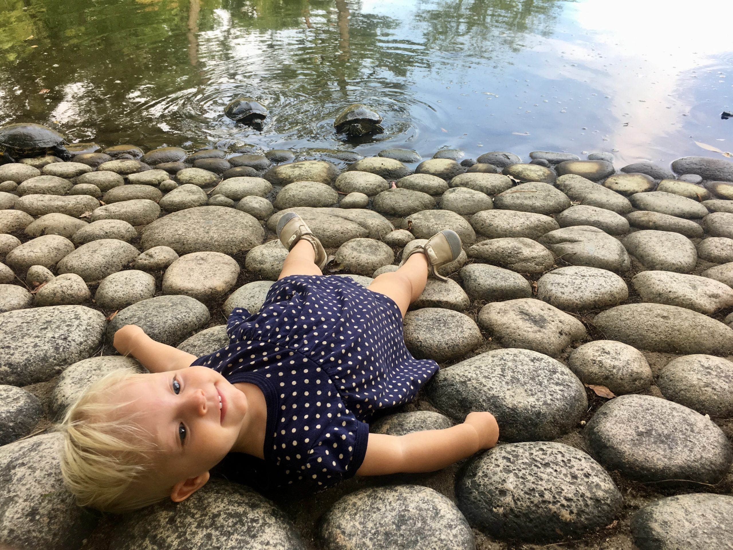 Toddler girl laying on stones by water in Japan