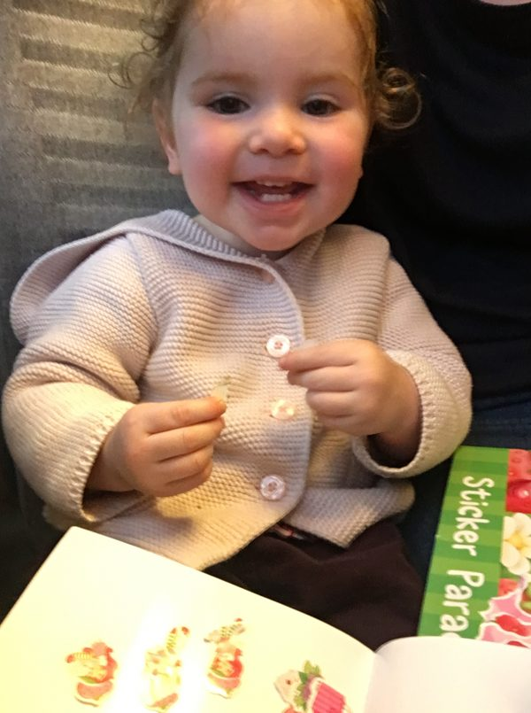 baby playing with stickers on train