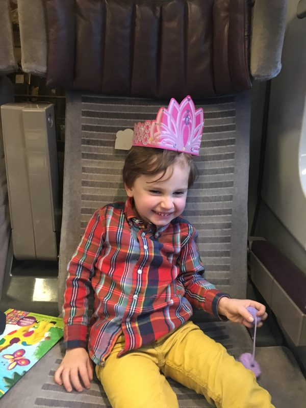 boy on eurostar wearing a paper crown