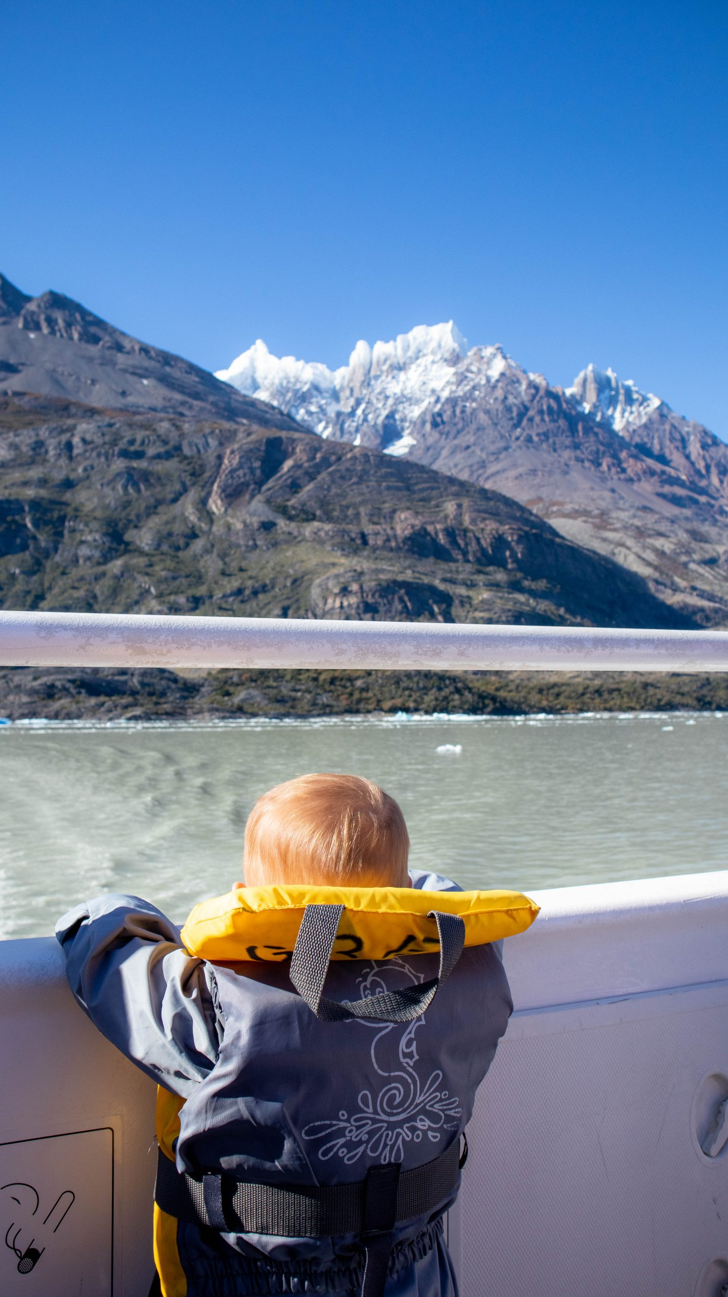 child on boat in front of Lago Grey