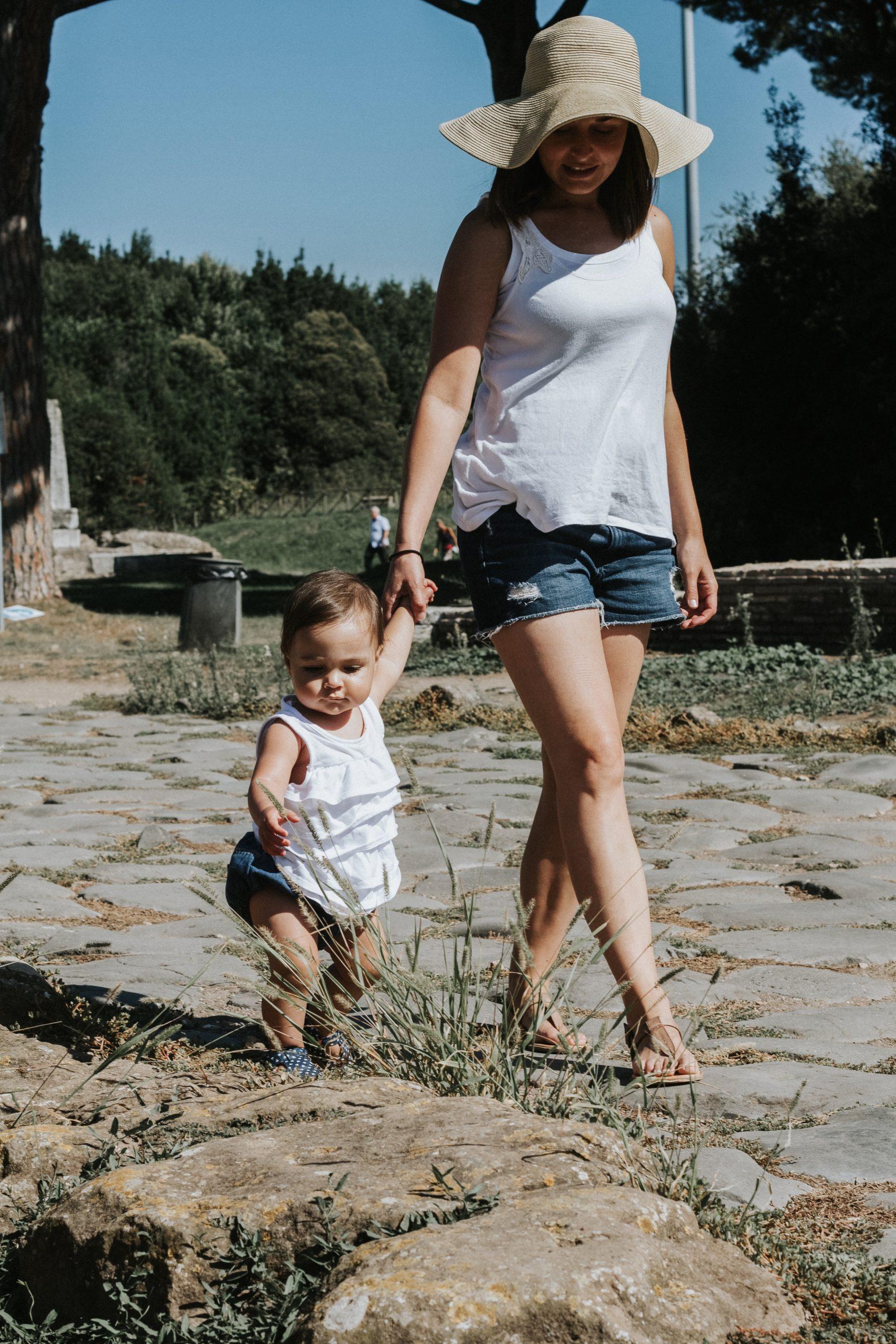 mom walking with baby through Ostia Antica