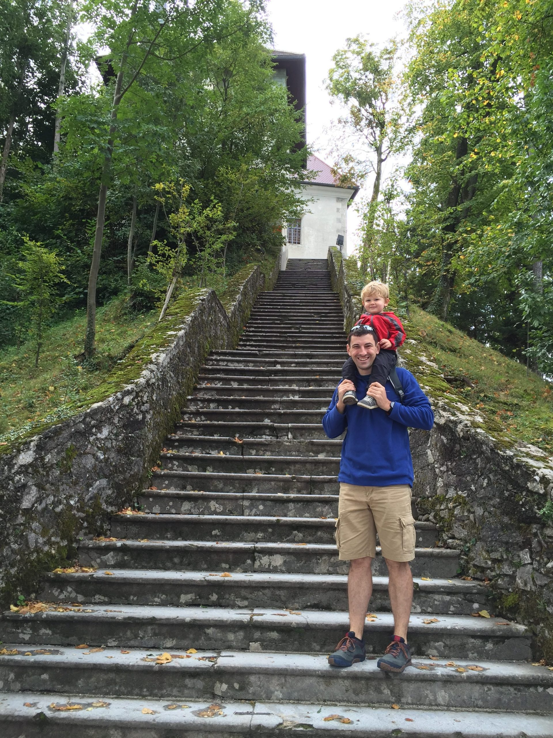 Father standing at steps in Lake Bled with son on his shoulders