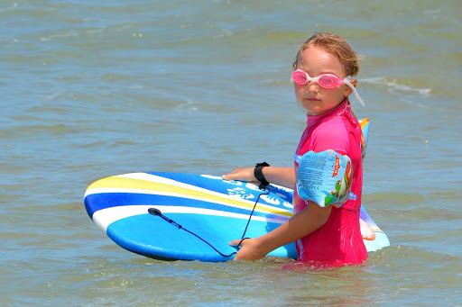 Young girl with a surfboard in water