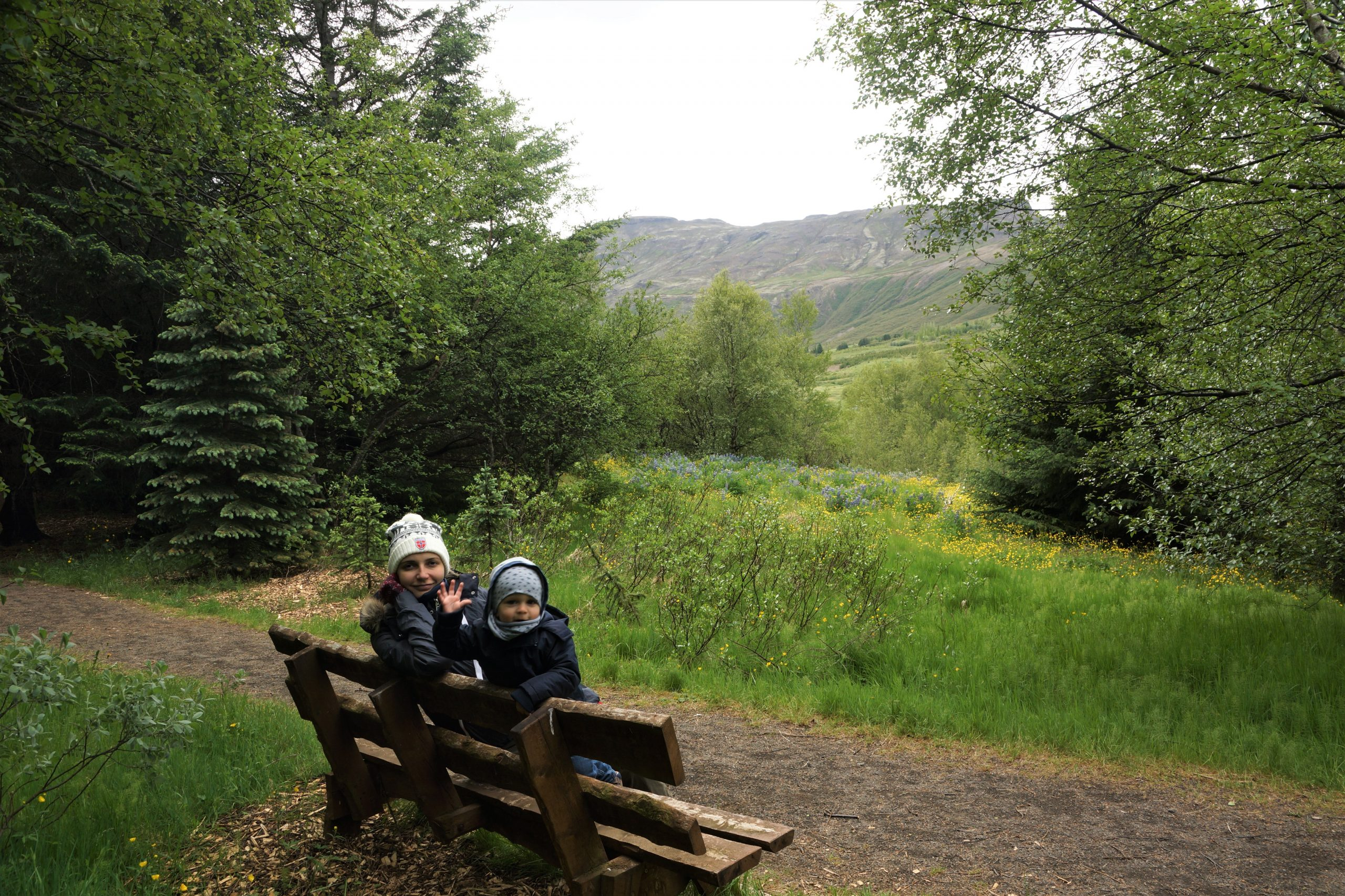 mother and toddler sitting on bench in nature