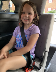 Stacey's daughter posing for the booster seat review in the Mifold