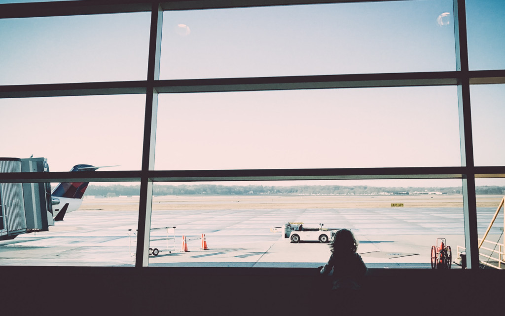toddler looking out at airport