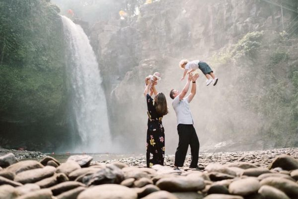 family with baby in front of waterfall ubud bali