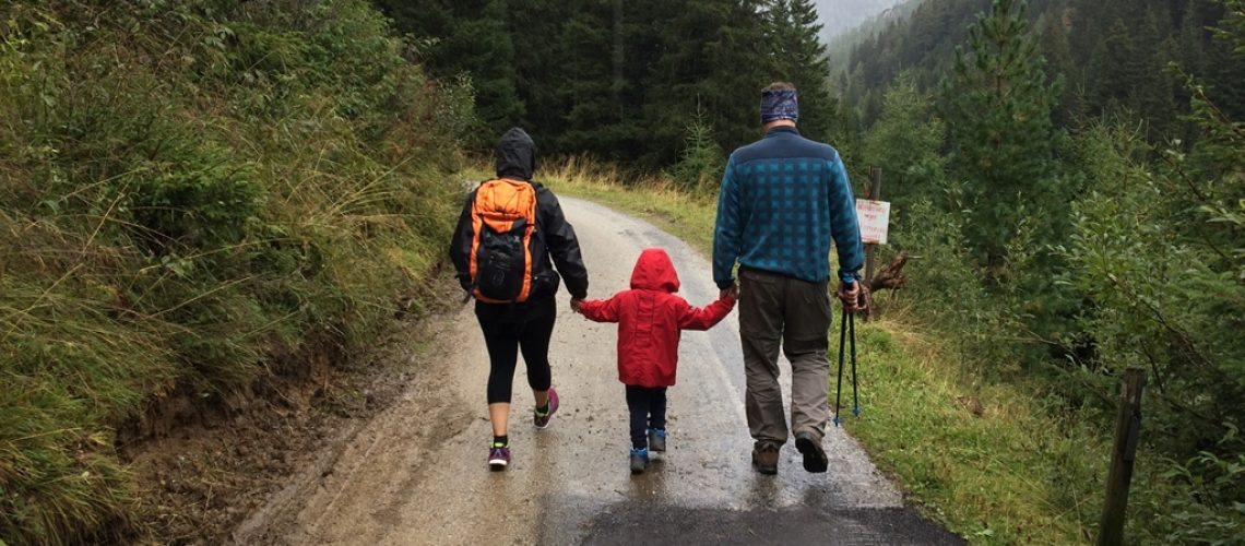 Family walking on a trail in the rain