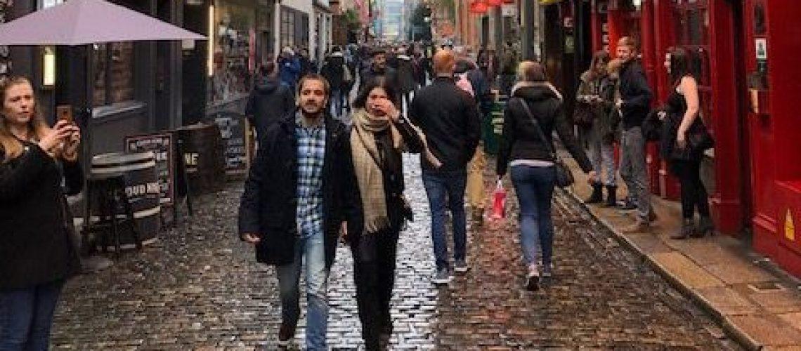 A couple walks through a crowded Dublin city street