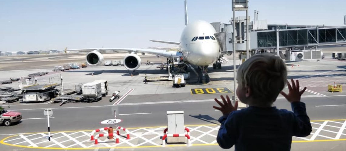Toddler looking at plane in airport in Abu Dhabi