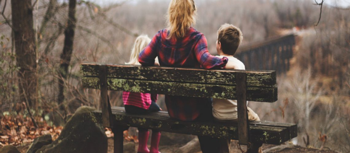 mom and kids on a bench in nature reserve in the UK norther england leeds